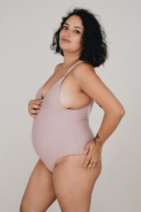 Model wearing light pink one piece holding her stomach.