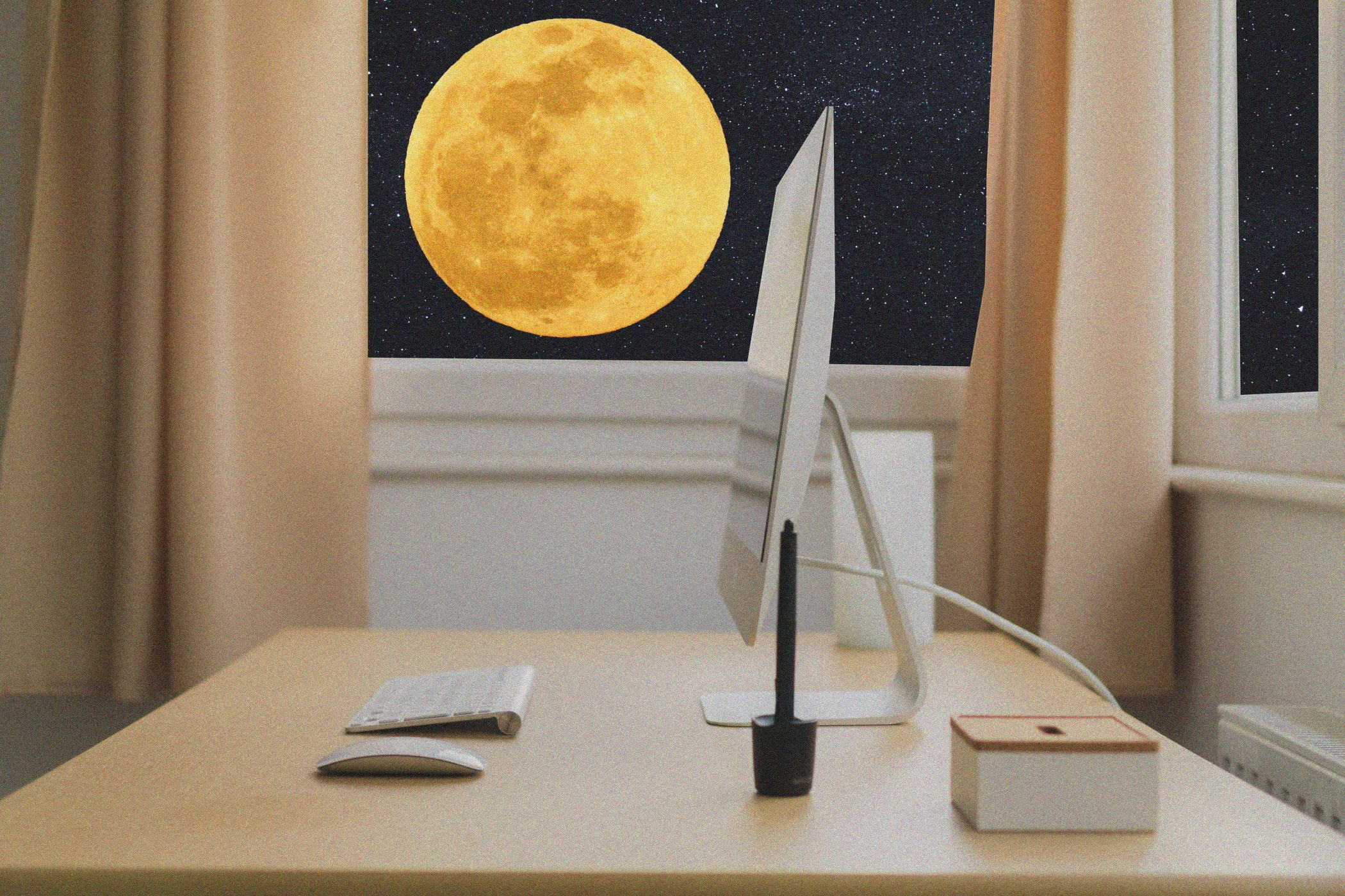 Desk with windows open showing the night sky with yellow full moon in background.